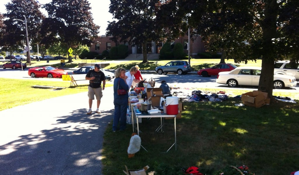A couple of people browsing items available at the church's table during the August 24th Yard Sale.